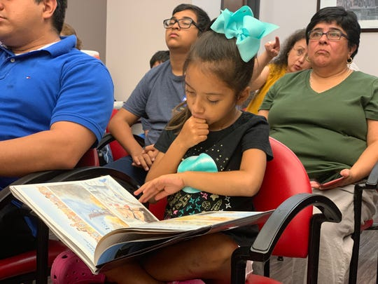 A girl reads a book about the first moon landing during the Back to the Moon discussion, which featured two NASA engineers at the Nueces County Keach Library on Saturday, Aug. 3 , 2019.
