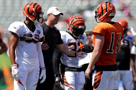 Cincinnati Bengals head coach Zac Taylor instructs Cincinnati Bengals quarterback Andy Dalton (14) in a huddle during Cincinnati Bengals training camp practice, Saturday, Aug. 3, 2019, at the practice fields next to Paul Brown Stadium in Cincinnati.