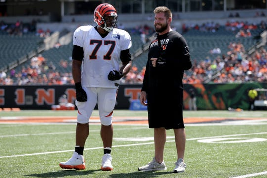 Cincinnati Bengals offensive tackle Cordy Glenn (77) talks with injured offensive tackle Jonah Williams, right, during Cincinnati Bengals training camp practice, Saturday, Aug. 3, 2019, at the practice fields next to Paul Brown Stadium in Cincinnati.