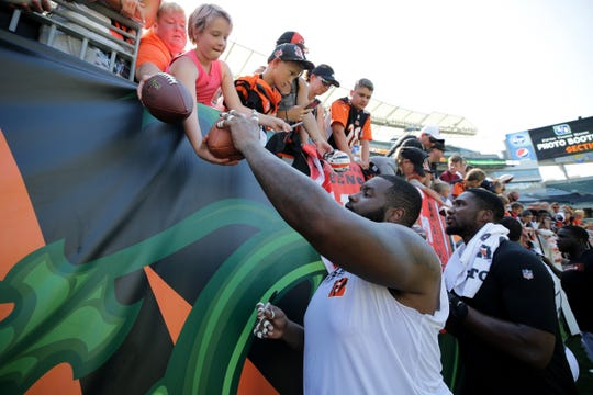 Cincinnati Bengals offensive tackle Andre Smith (71) signs autographs for fans during Cincinnati Bengals training camp practice, Saturday, Aug. 3, 2019, at the practice fields next to Paul Brown Stadium in Cincinnati.