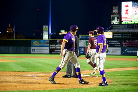 Johnston's Peyton Williams (24), left, and Johnston's Reece Anderson (12) celebrate scoring a run during their 4A state baseball semi-final game on Friday, Aug. 2, 2019 in Des Moines. Johnston would go on to defeat Dowling Catholic 7-0 to advance to the finals on Saturday.
