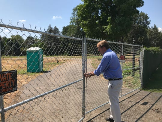 Luxury homebuilder Richard Russell locks a gate on Aug. 2 at the 8-acre site he plans to develop in Grosse Pointe Shores.