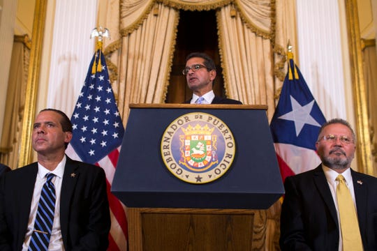 Pedro Pierluisi, sworn in as Puerto Rico's governor, speaks during a press conference, in San Juan, Puerto Rico, Friday, Aug. 2, 2019. Departing Puerto Rico Gov. Ricardo Rossello resigned as promised on Friday and swore in Pierluisi, a veteran politician as his replacement, a move certain to throw the U.S. territory into a period of political chaos that will be fought out in court. Pierluisi is flanked by lawmakers Jorge Navarro, left and Jose Aponte.