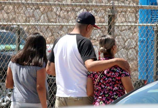People walk out of an elementary school after family members were asked to reunite following a shooting  at a shopping mall in El Paso, Texas, on Saturday, Aug. 3, 2019.   Multiple people were killed and one person was in custody after a shooter went on a rampage at a shopping mall, police in the Texas border town of El Paso said.