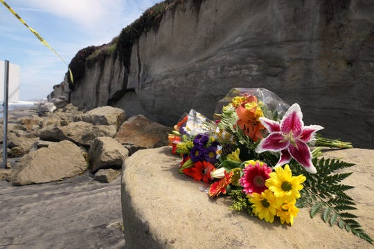 A bouquet of flowers lies on some of the sand rock debris from Friday's bluff collapse, which killed three people, near the Grandview Beach access stairway in the beach community of Leucadia, Saturday, Aug. 3, 2019, in Encinitas, Calif.