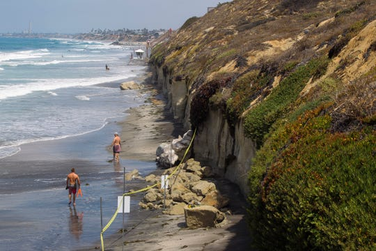 The area where Friday's sea cliff collapsed killing three people is taped off near the Grandview Beach access stairway in the beach community of Leucadia, Saturday, Aug. 3, 2019, in Encinitas, Calif. A 30-foot-long hunk of the cliff in San Diego County collapsed Friday afternoon. Rescuers rushed to dig out victims, but a woman died at the scene and two more victims died at hospitals.
