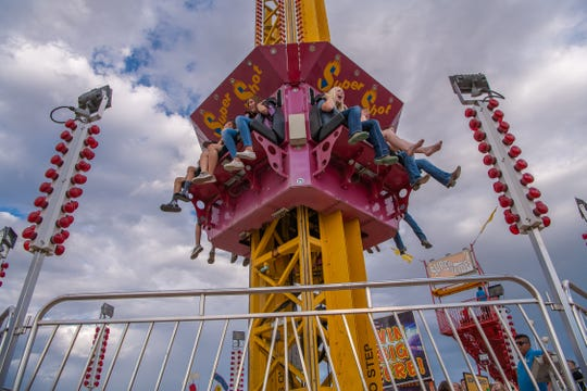 Attendees enjoy a carnival ride at the Larimer County Fair on Friday, August 2, 2019, in Loveland, Colo.