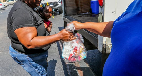Zymir Williams goes with her grandmother to pick up their free lunch during a recent summer feeding program.