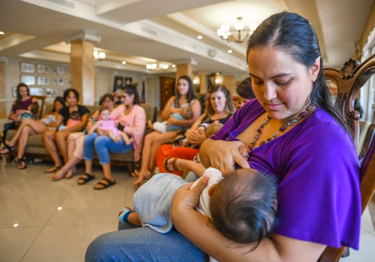 Dr. Mariana Cook-Huynh breastfeeds her son, Tate Huynh, as she and other breastfeeding mothers participate in the 10th annual Global Big Latch On event at the Government House in Agana Heights on Saturday, Aug. 3, 2019. During the event, Gov. Lou Leon Guerrero, Cook-Huynh's mother, signed a proclamation to celebrate the month of August as Guam Breastfeeding Awareness Month.
