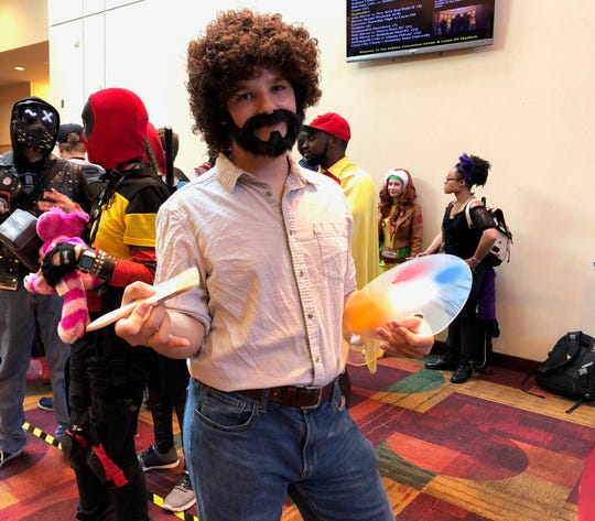 Bob Ross shows off his easel and paint brush on Saturday at Gen Con.