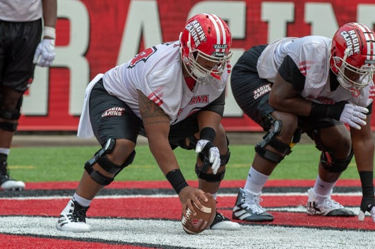 Shane Vallot (64) works at center as the Ragin' Cajuns open preseason camp Friday night.