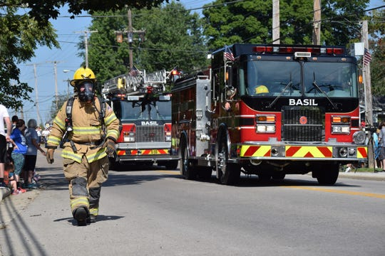 A firefighter in full gear walks with the Basil Joint Fire District's truck in the Baltimore Festival parade Saturday.
