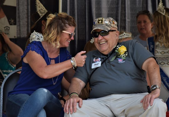 This year's Hometown Heroes, Jo Del Landis and Joseph Machado, share a laugh on stage after Saturday's parade during the Baltimore Festival.