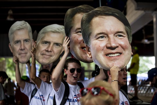 "Cheers and jeers rained down on a group from ""Team Mitch,"" who marched through the crowd with Brett Kavanaugh and Neil Gorsuch heads at the Fancy Farm Picnic. Aug. 3, 2019"