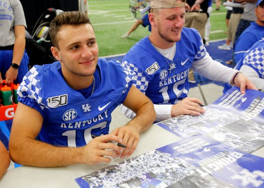 Nik Scalzo, left, and Kolbe Langhi sign posters during Kentucky football's Fan Day at the Nutter Field House on campus.