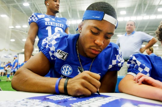 Bryce Oliver signs a poster during Kentucky football's Fan Day at the Nutter Field House on campus.
