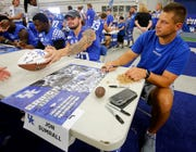 Coach Jon Sumrall, right, signs autographs during Kentucky football's Fan Day at the Nutter Field House on campus.