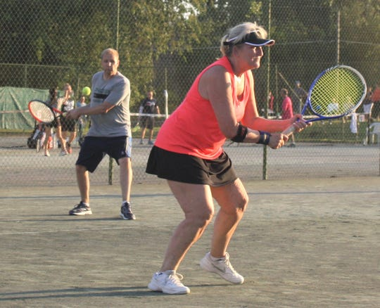 Brad Forster returns a shot from the baseline while his partner, Mary Ellison, stands guard at the net during Friday's mixed doubles competition in the 86th News Journal/Richland Bank Tennis Tournament at Lakewood Racquet Club.