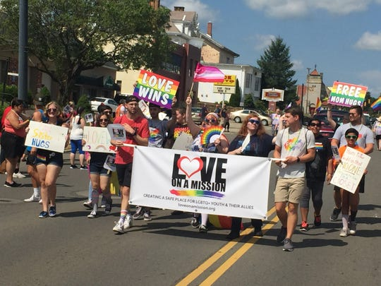 People representing Love on a Mission march in the Mansfield Gay Pride parade on Saturday morning.