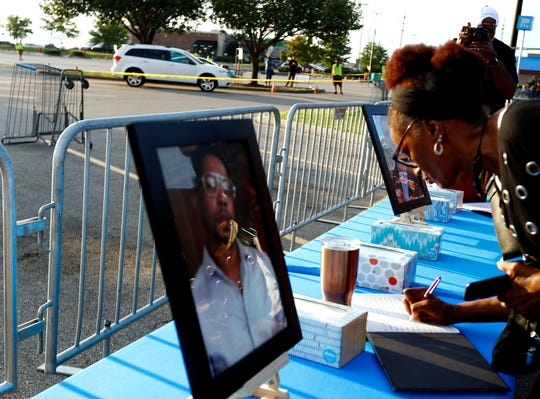 A woman signs a book Friday night,  August 2, 2019, in front of a photo of Brandon Gales who was killed in a shooting at the Southaven Walmart on Tuesday, July 30.