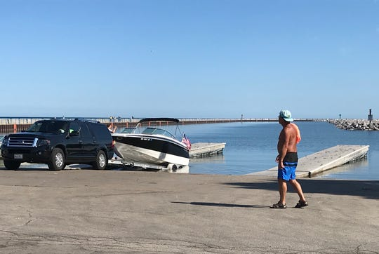 Bob Muschelewicz of New Berlin backs his boat into the water at a launch near McKinley Marina in Milwaukee on Thursday. The docks there are sloping upward at their ends because of high water levels on Lake Michigan.