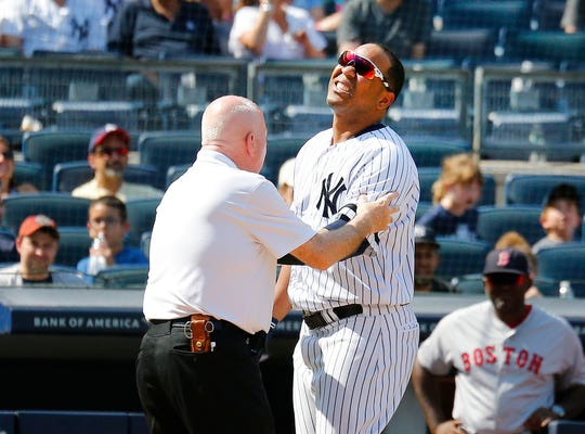 Aug 3, 2019; Bronx, NY, USA; New York Yankees designated hitter Edwin Encarnacion (30) is examined by trainer Steve Donohue after being hit by a pitch against the Boston Red Sox during the eighth inning of game one of a doubleheader at Yankees Stadium.
