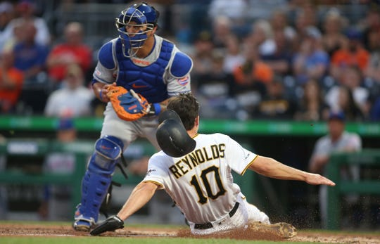 Pittsburgh Pirates left fielder Bryan Reynolds (10) slides across home plate to score a run as New York Mets catcher Wilson Ramos (40) waits for a late throw during the fourth inning at PNC Park.