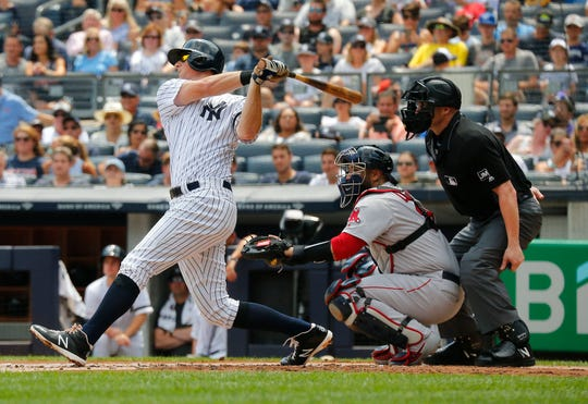 Aug 3, 2019; Bronx, NY, USA; New York Yankees first baseman DJ LeMahieu (26) hits a solo home run against the Boston Red Sox during the first inning of game one of a doubleheader at Yankees Stadium.
