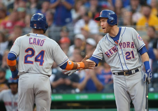 New York Mets third baseman Todd Frazier (21) greets second baseman Robinson Cano (24) crossing home plate to score a run against the Pittsburgh Pirates during the third inning at PNC Park.