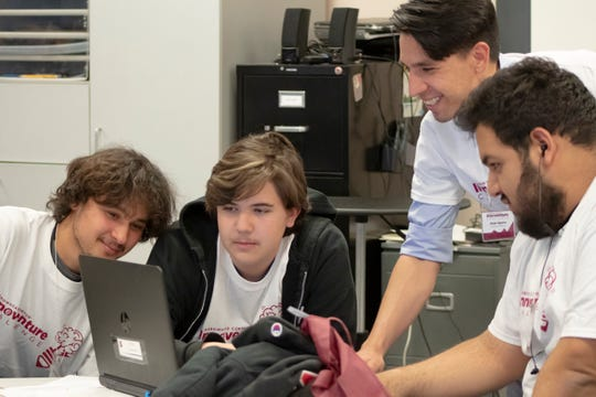 New Mexico State University College of Business alum Jorge Aguirre, standing, talks with Innoventure High School Challenge competitors, from left: Adam Duenas, Colton Montoya and Nathan Rubalcava, all students at Gadsden High School.