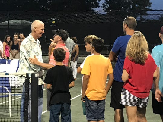 "Brian Sakey shares a warm embrace with fellow Roger Scott pro tennis player Josh Koivu on ""Matey Night."""