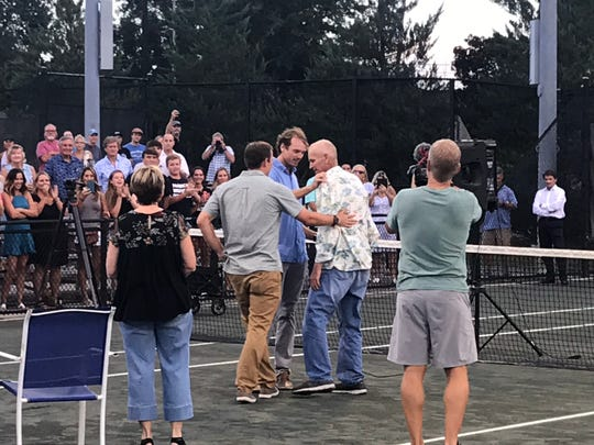 Brian Sakey is flanked by sons Brock and Ross Sakey as the crowd watches at Roger-Scott Tennis Center.