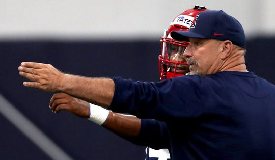 Offensive coordinator Noel Mazzone gives quarterback Khalil Tate some one-on-one pointers while running the quarterbacks through their paces during Thursday's practice.