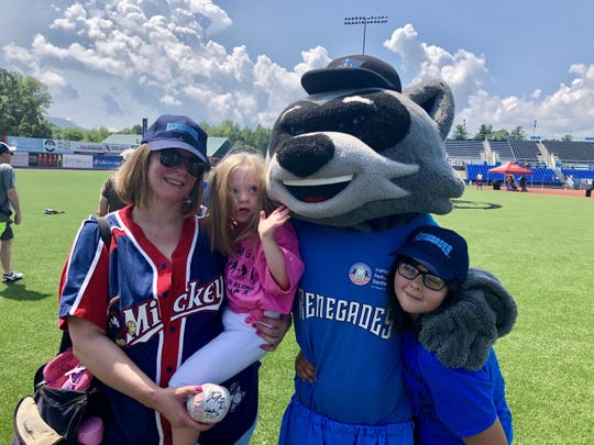 Molly Carroll, a 6-year-old from Poughkeepsie, poses with her mother and sister alongside Rascal, the Hudson Valley Renegades mascot during the Disability, Dream & Do baseball camp Saturday.