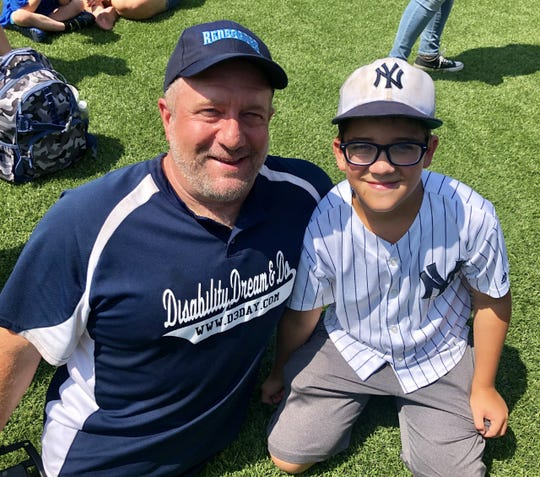 Dave Stevens poses alongside his son, Luke, during the Disability Dream & Do baseball camp Saturday at Dutchess Stadium. Dave Stevens, who helped organize the event, was born without legs.