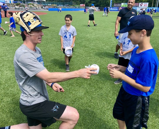 Hudson Valley Renegades shortstop Nick Sogard autographs a ball for Vidal Feliz of Beacon during Saturday's Disability, Dream & Do baseball camp at Dutchess Stadium.