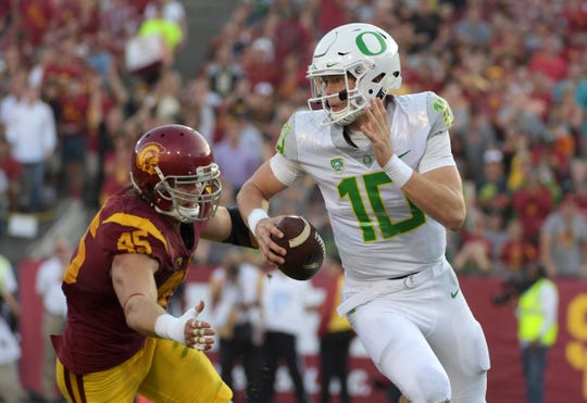 Oregon quarterback Justin Herbert (10) is pressured by Southern California defensive end Porter Gustin (45) during a game at Los Angeles Memorial Coliseum on Nov. 5, 2016.