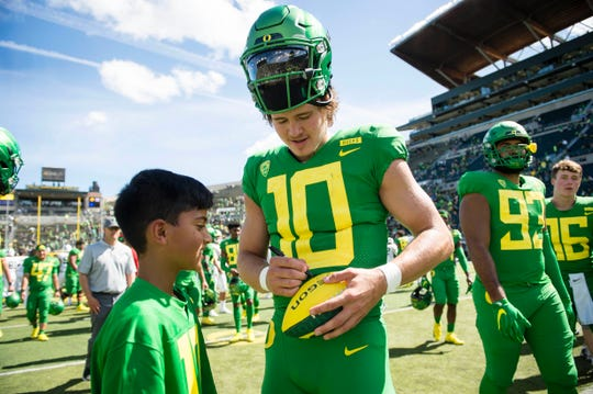 Oregon quarterback Justin Herbert (10) signs a football for a fan after a game against Portland State on Sept. 8, 2018.