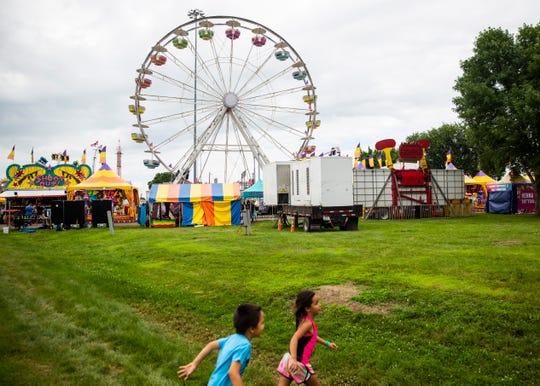 Kids run across the grass at W.H. Lyon fairgrounds during the Sioux Empire Fair, Saturday, Aug. 3.