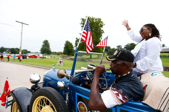 Abraham Clark of the Cherokee Nation blows a horn while Shurita Thomas-Tate waves to the crowd as they ride in a vintage car during the annual Park Day Reunion Parade on Saturday, Aug. 3, 2019.