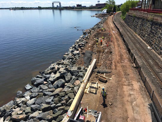 Crews rebuild a stretch of the Lakewalk behind the Fitger's building June 28, 2019, in downtown Duluth.