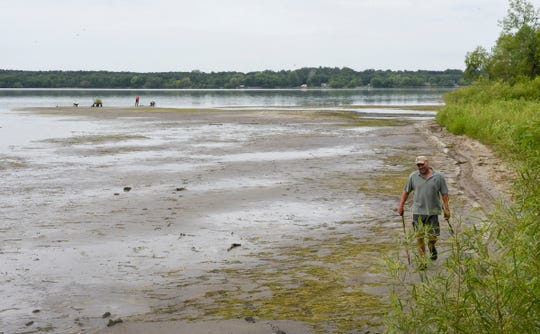 Eric Altena of the Minnesota Department of Natural Resources walks along the beach at Benton Beach Campground around 10 a.m. Friday, Aug. 2, 2019. The drawdown's effects increased significantly from the previous afternoon, with volunteers beginning planting efforts Friday.