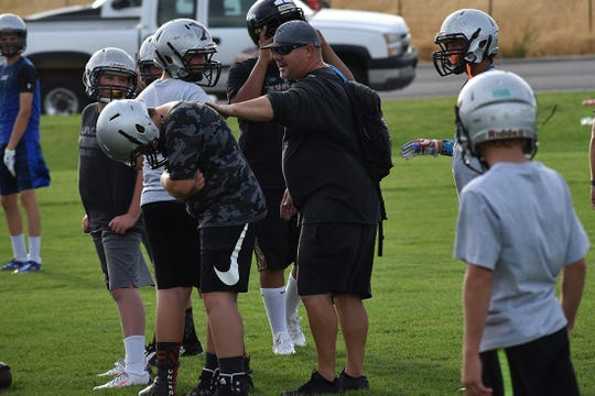 Canyon View coach Chris Sawyers coaches youth football players during C.V.'s youth camp.