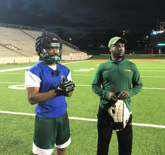 FAMU wide receiver Marcus Williams (left) and graduate assistant coach Myron Dillard watch the action on the field at practice.