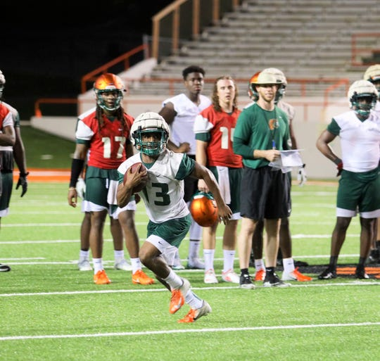 FAMU running back Bishop Bonnett dashes off with the ball during the first day of practice on Friday, Aug. 2, 2019.
