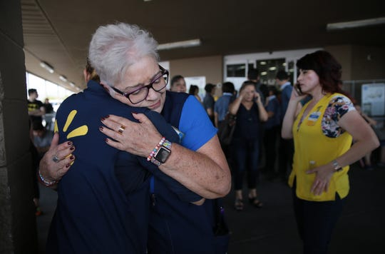 WalMart employees comfort one another after an active shooter opened fire at the WalMart near Cielo Vista Mall in El Paso Saturday.