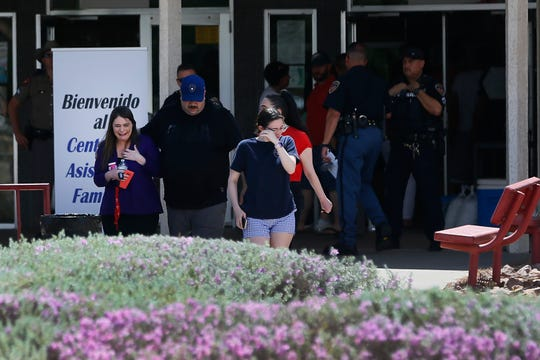 People arrive at MacArthur Elementary looking for family and friends as the school is being used a re-unification center during the aftermath of a shooting at the Walmart in the Cielo Vista Mall area Saturday, Aug. 3, in El Paso.