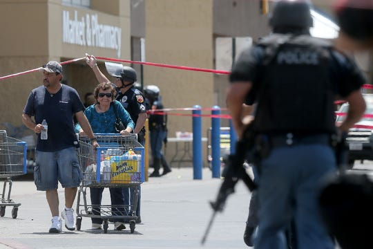 Walmart customers are escorted from the store after a gunman opened fire on shoppers Saturday, Aug. 3, 2019, at the store near Cielo Vista Mall in El Paso, Texas.