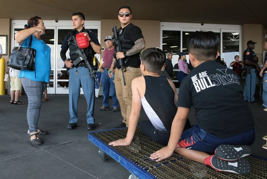 Police interview witnesses as their children watch at Sam's Club, where Walmart shoppers were evacuated during the mass shooting at Walmart near Cielo Vista Mall in El Paso on Saturday, Aug. 3, 2019.