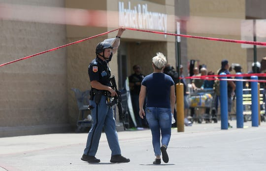 An employee crosses into the crime scene at an active shooter event at Walmart near Cielo Vista Mall in El Paso on Saturday, Aug. 3, 2019.